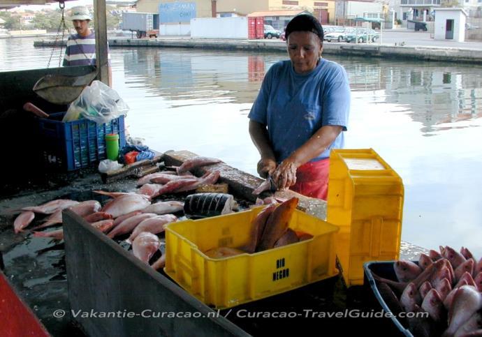 Vismarkt - Vrouw maakt verse vis schoon